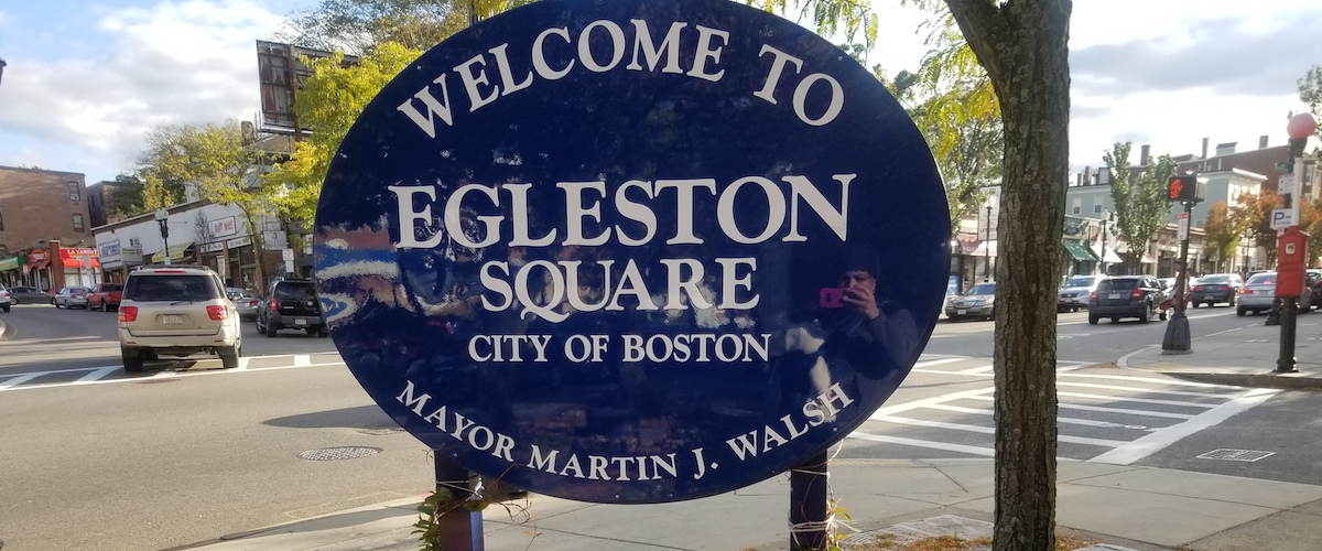 "An oval-shaped blue sign that reads ""Welcome to Egleston Square City of Boston Mayor Martin J. Walsh"" in front of a parking lot and trees."